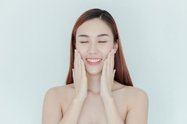 Mulher jovem e bonita com pele fresca limpa toque próprio rosto. tratamento facial. cosmetologia, beleza e spa