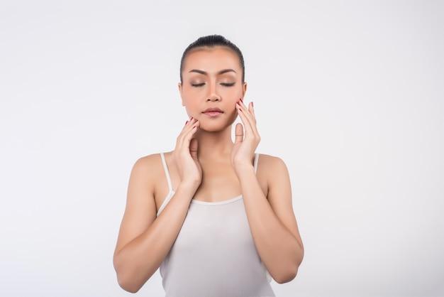 Mulher jovem e bonita com pele fresca limpa toque próprio rosto