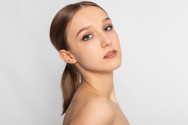 Mulher jovem e bonita com pele limpa e fresca desviar o olhar. cuidados com o rosto de beleza feminina. tratamento facial. cosmetologia, beleza e spa.