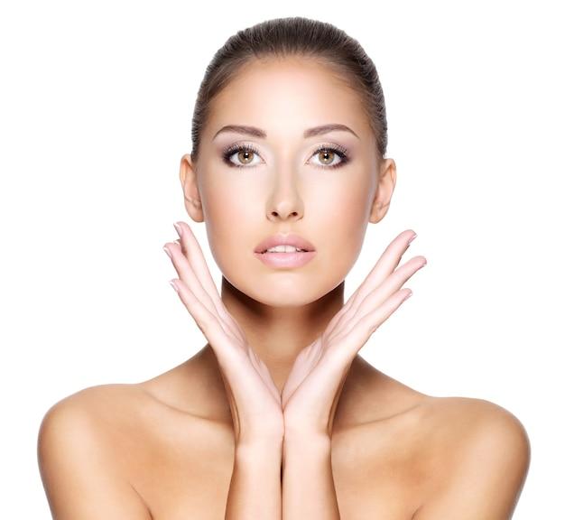 Mulher jovem e bonita com pele limpa e fresca que quer tocar seu rosto com as duas mãos, isolado no branco