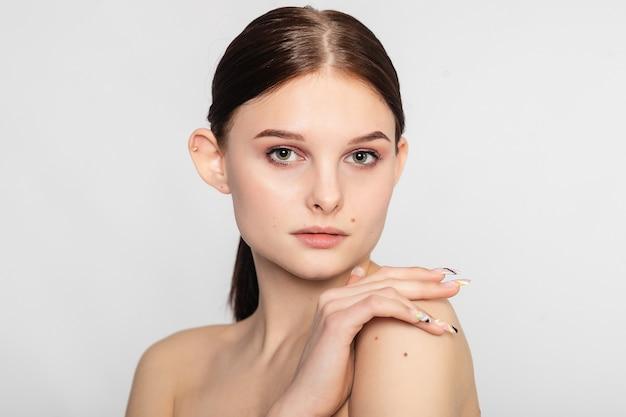 Mulher jovem e bonita com pele limpa, fresca e morena ouvir tocar seu próprio rosto com a mão direita olhando diretamente. cosmetologia, beleza e spa. cuidados com o rosto.