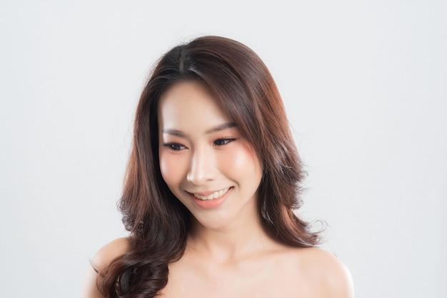 Mulher jovem e bonita com pele limpa, fresca em cinza