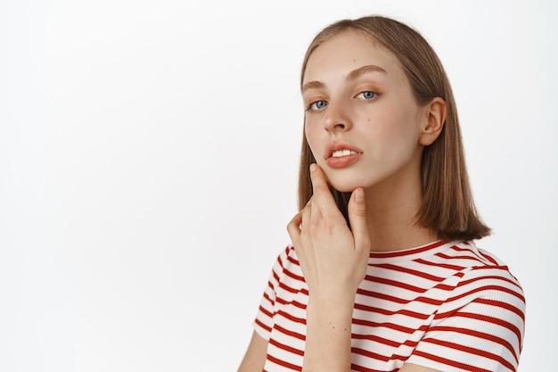 Mulher jovem e bonita com pele limpa, natural e perfeita, sem acne e maquiagem, tocando o rosto e parecendo sensual na frente, em pé contra uma parede branca.