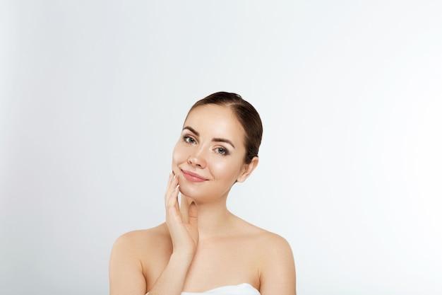 Mulher jovem e bonita com pele limpa, perfeita. retrato da modelo de beleza com maquiagem nude natural e tocando seu rosto. spa, cuidados com a pele e bem-estar. close up, copyspace.