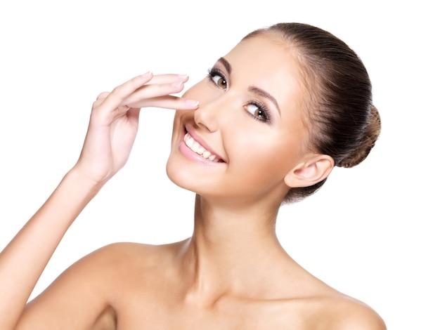 Mulher jovem e bonita com pele limpa perfeita tocando seu nariz e sorrindo, isolada no branco