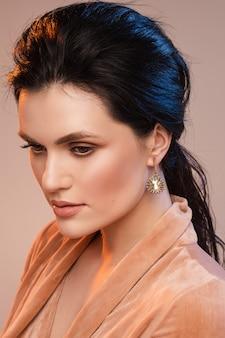Mulher jovem e bonita com pele saudável, maquiagem perfeita, cabelos longos morena, brinco elegante. conceito de beleza natural.
