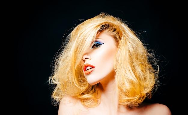 Mulher jovem e bonita com penteado e maquiagem pin-up. retrato de uma jovem bela mulher sexy com penteado e maquiagem glamourosa, em fundo preto.