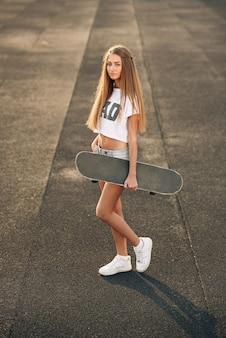 Mulher jovem e bonita com piercing em uma camiseta branca, shorts e tênis branco em pé com skate nas mãos
