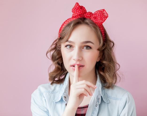 Mulher jovem e bonita com pin-up maquiagem e penteado. studio atirou em fundo rosa