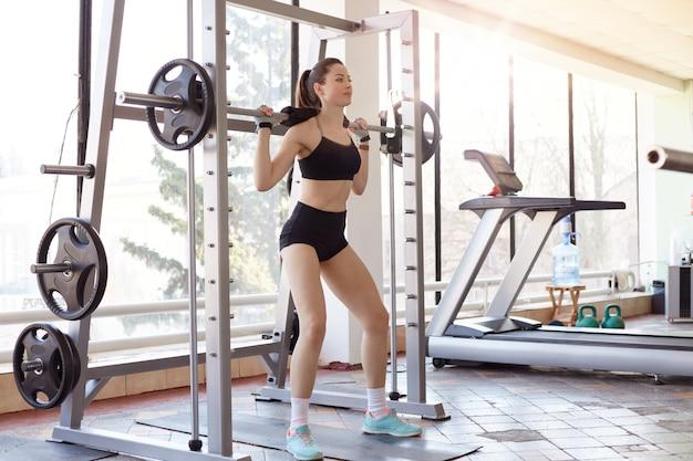 Mulher jovem e bonita com placas de barra e peso em cima. atleta feminina com rabo de cavalo, levantamento de pesos pesados. modelo de fitness caucasiano exercitando na academia.
