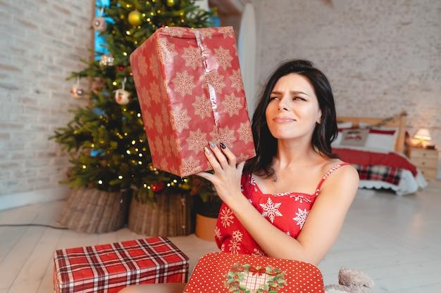 Mulher jovem e bonita com presentes na árvore de natal
