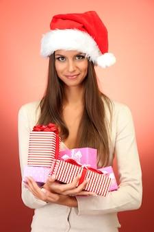 Mulher jovem e bonita com presentes, sobre fundo vermelho