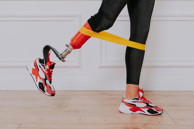 Mulher jovem e bonita com prótese de perna fazendo exercícios