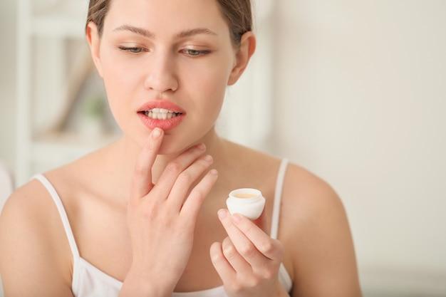 Mulher jovem e bonita com protetor labial em casa