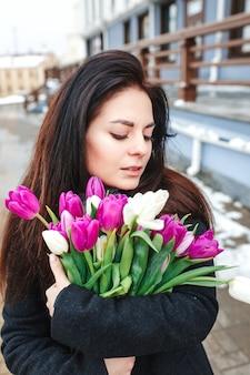 Mulher jovem e bonita com retrato ao ar livre de flores, garota primavera segurar buquê fresco, elegante senhora elegante, fêmea de beleza bonita morena na rua da cidade