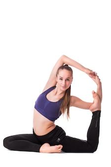 Mulher jovem e bonita com roupa ativa branca fazendo exercícios de ioga em fundo branco