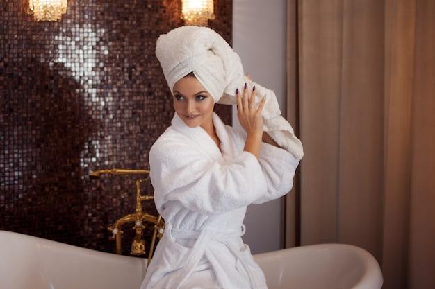 Mulher jovem e bonita com roupão e toalha na cabeça. garota depois do banho