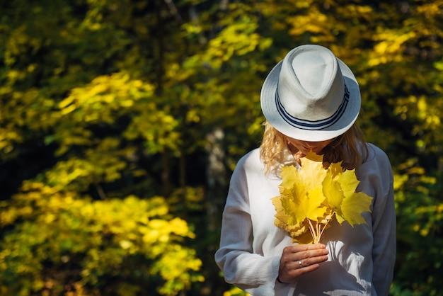 Mulher jovem e bonita com roupas brancas e chapéu inclinou a cabeça para o buquê de folhas amarelas em suas mãos