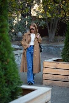 Mulher jovem e bonita com roupas da moda em uma caminhada na cidade de outono