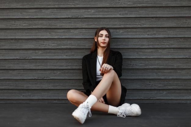 Mulher jovem e bonita com roupas da moda sentada perto de uma parede de madeira
