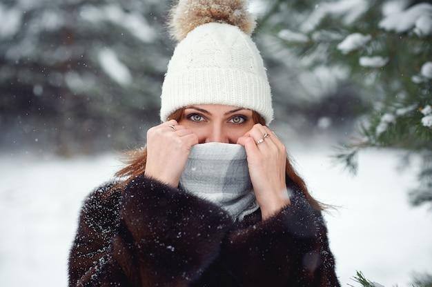 Mulher jovem e bonita com roupas de malha de inverno quente cobriu o rosto com um lenço, segurando as mãos na frente do nariz e olhando