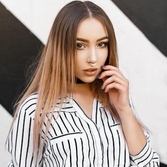 Mulher jovem e bonita com roupas elegantes perto da parede