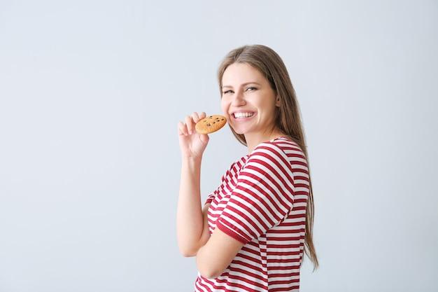 Mulher jovem e bonita com saboroso biscoito cinza