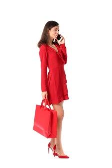 Mulher jovem e bonita com sacola de compras falando ao celular em branco