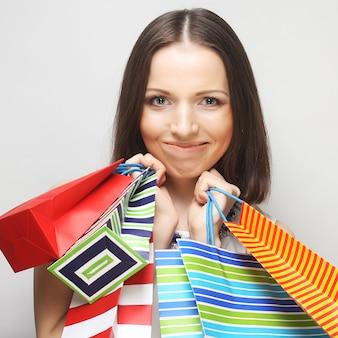 Mulher jovem e bonita com sacolas coloridas