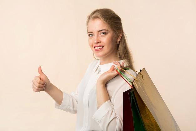 Mulher jovem e bonita com sacolas de compras no fundo branco