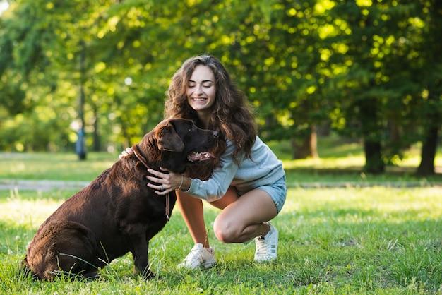 Mulher jovem e bonita com seu cachorro no jardim