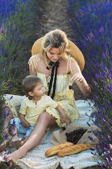 Mulher jovem e bonita com seu filho fofo em um campo de lavanda