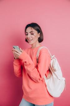 Mulher jovem e bonita com smartphone. aluna sorridente em uma viagem.