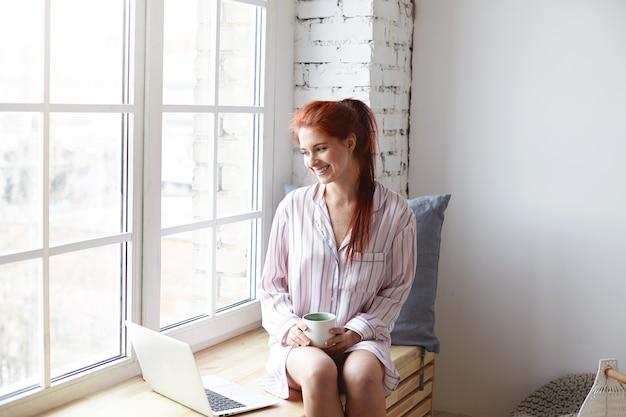 Mulher jovem e bonita com sorriso fofo e cabelo ruivo em rabo de cavalo, desfrutando de uma manhã lenta em casa, sentada perto de uma janela grande, bebendo café, navegando na internet no laptop. sol diurno, cores suaves