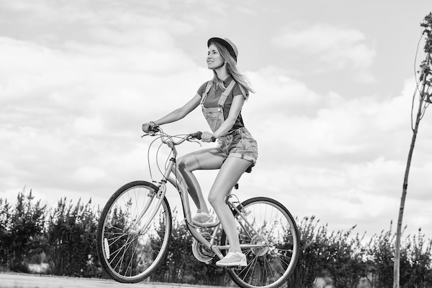 Mulher jovem e bonita com sua bicicleta no parque