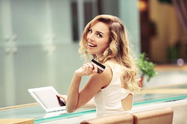 Mulher jovem e bonita com tablet digital e cartão de crédito no café