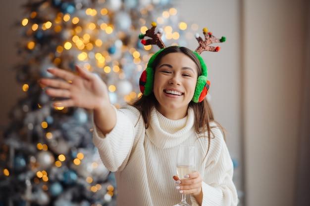 Mulher jovem e bonita com taça de champanhe em casa. celebração do natal
