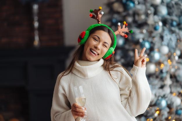 Mulher jovem e bonita com taça de champanhe em casa