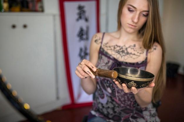 Mulher jovem e bonita com tatuagem de heena jogando tibetano cantando tigela na natureza