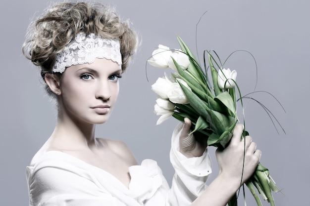 Mulher jovem e bonita com tulipas brancas