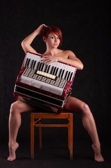 Mulher jovem e bonita com um acordeão vermelho posando enquanto está sentado em uma cadeira