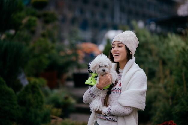 Mulher jovem e bonita com um cachorro branco