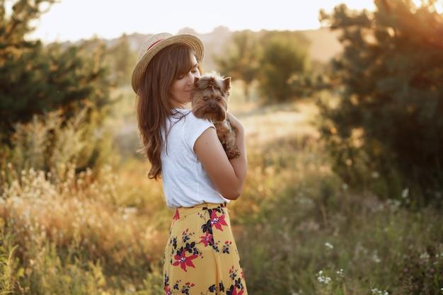 Mulher jovem e bonita com um cachorro no campo de verão
