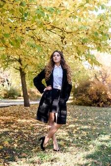 Mulher jovem e bonita com um casaco de pele na floresta mágica de outono.