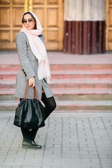 Mulher jovem e bonita com um casaco e uma bolsa posando