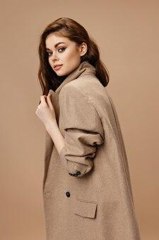 Mulher jovem e bonita com um casaco sobre fundo bege endireita a gola