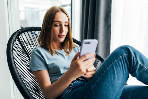 Mulher jovem e bonita com um celular sentada em uma cadeira perto da janela em casa