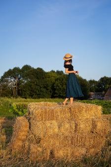 Mulher jovem e bonita com um chapéu de palha em pé sobre uma grande pilha de fardos de palha