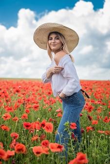 Mulher jovem e bonita com um chapéu de palha em um campo de papoulas no verão. beleza natural
