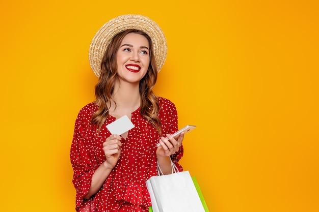 Mulher jovem e bonita com um chapéu de palha vermelho vestido de verão possui um telefone celular e um cartão de crédito nas mãos dela isolado em um banner de web de maquete de parede amarelo. garota faz compras on-line